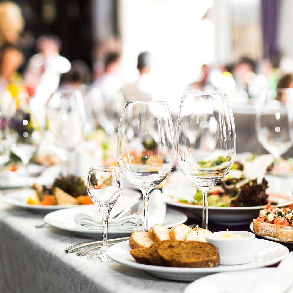 Geschirr mit Essen und Menschen im Hintergrund