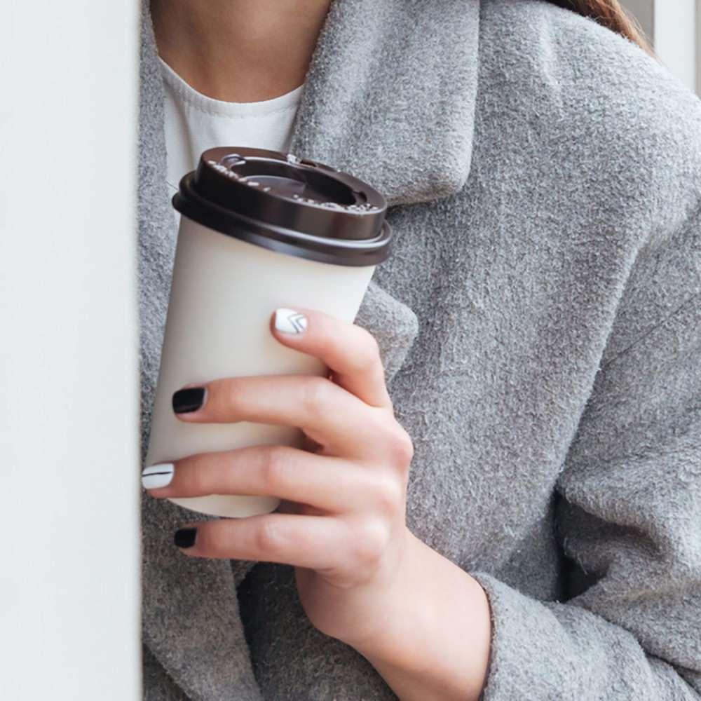 Kaffebecher 2Go wird in einer Hand gehalten